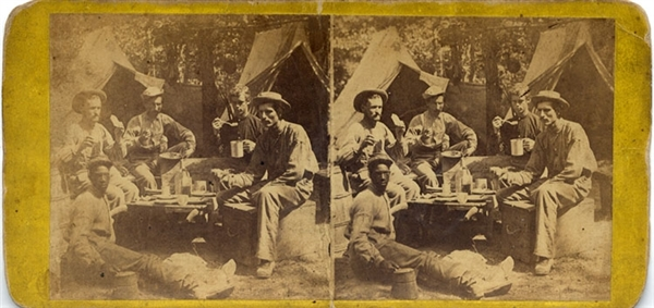 A terrific close-up of five men including an African American dining in camp